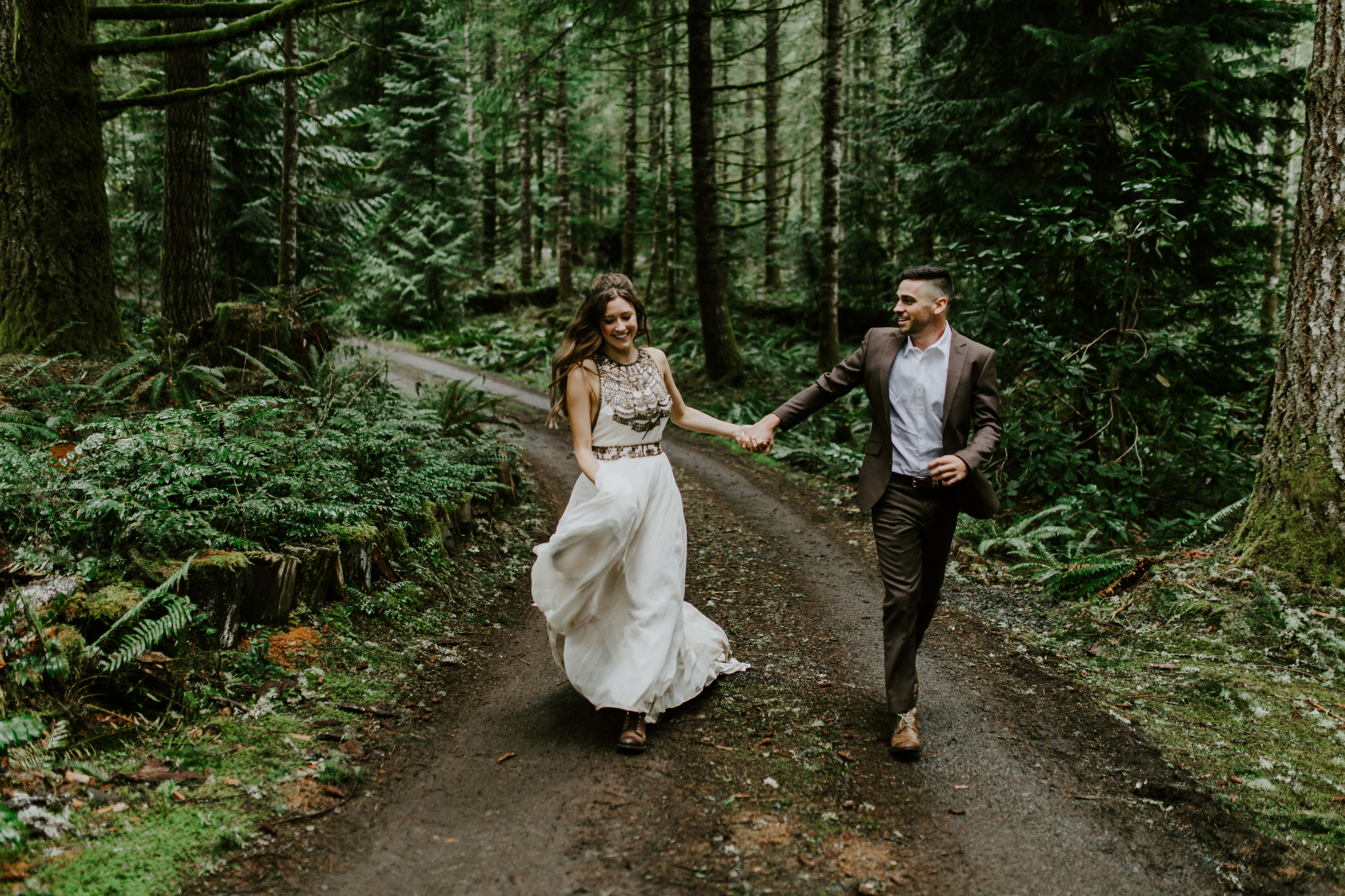 A couple runs down a path after their elopement.