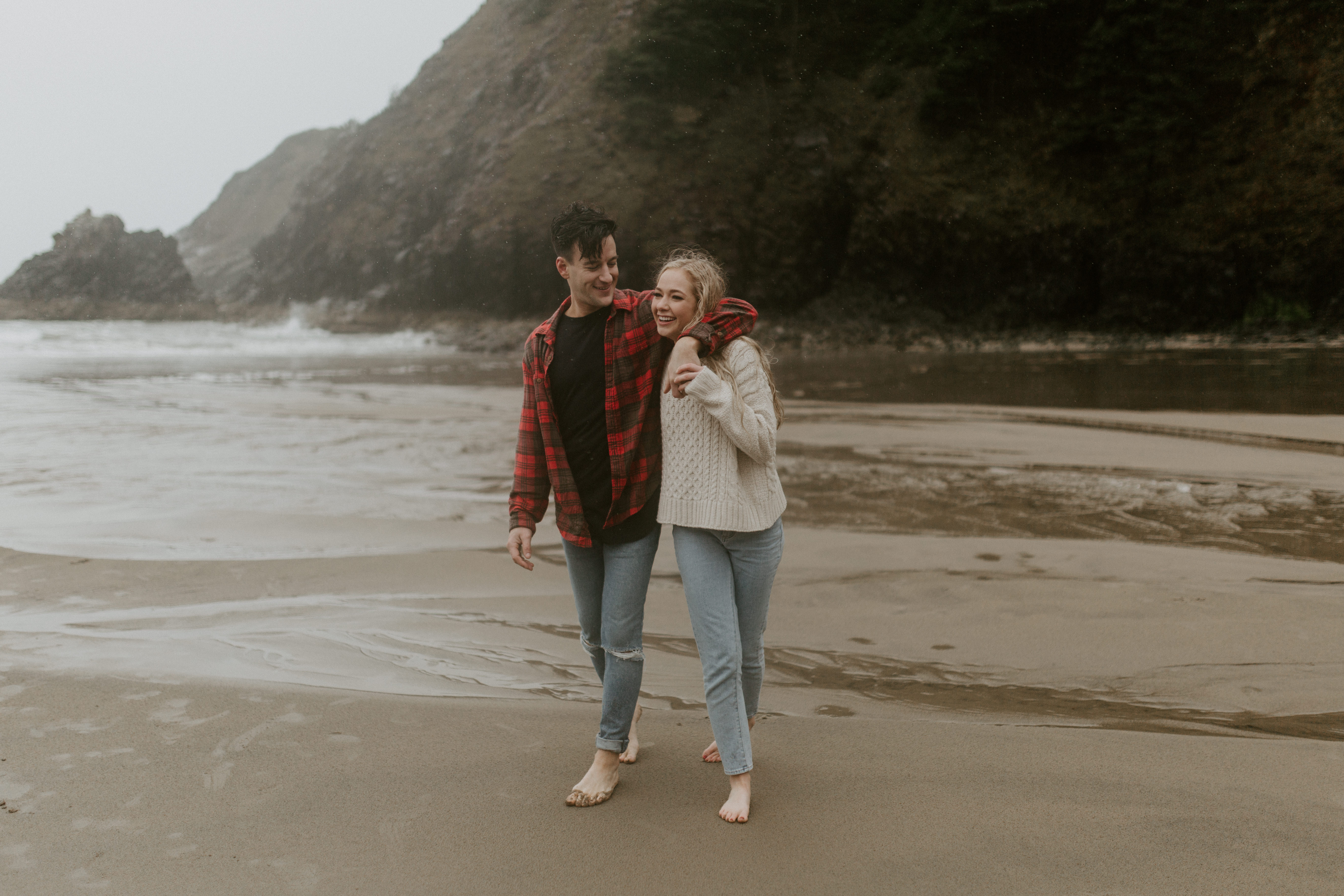 Hannah pulls Grant towards the waves on Indian Beach in Ecola State Park, Oregon. Engagement photography in Oregon by Sienna Plus Josh.