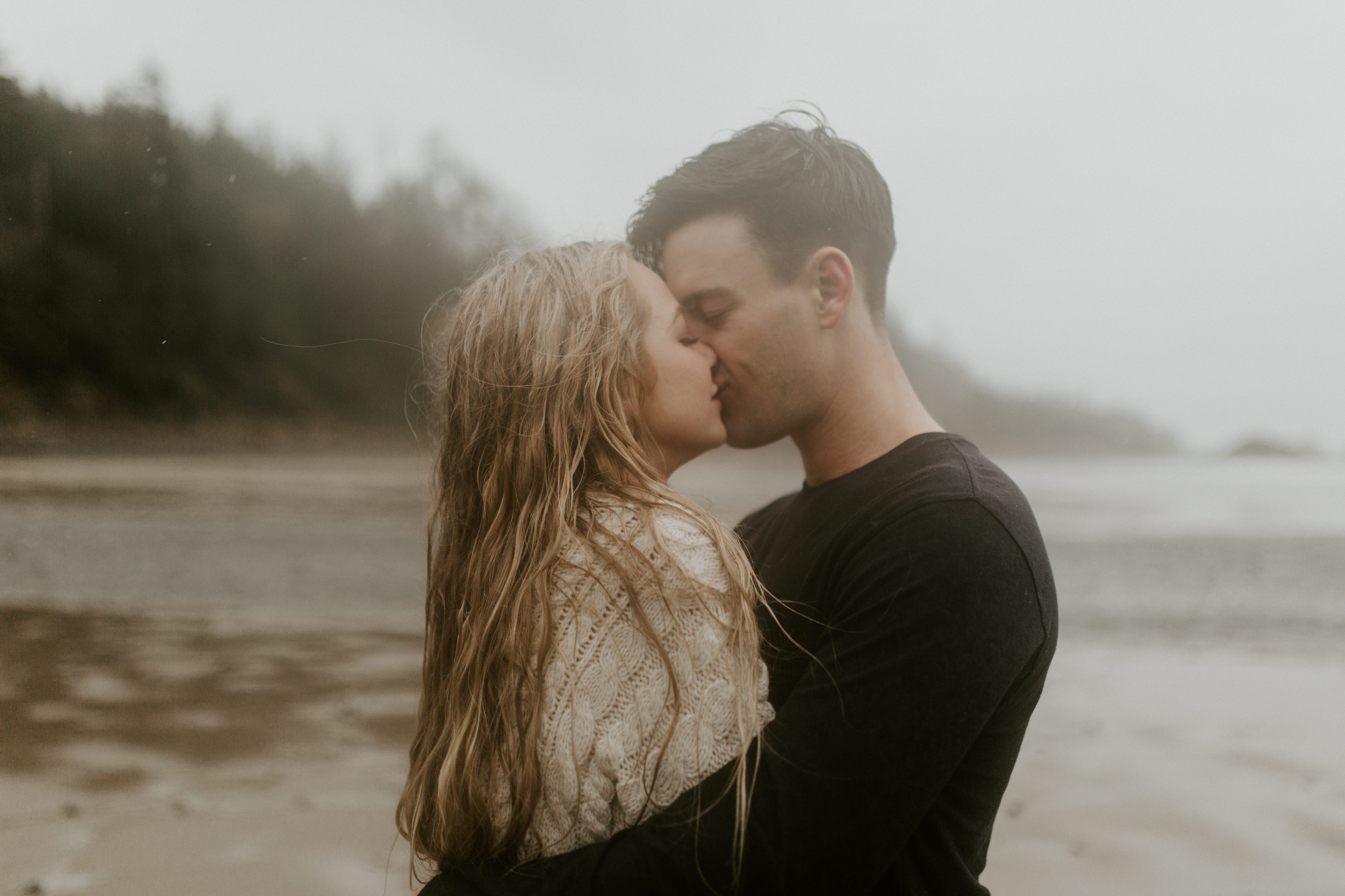 Hannah and Grant kiss in the rain on Indian Beach in Ecola State Park, Oregon. Engagement photography in Oregon by Sienna Plus Josh.
