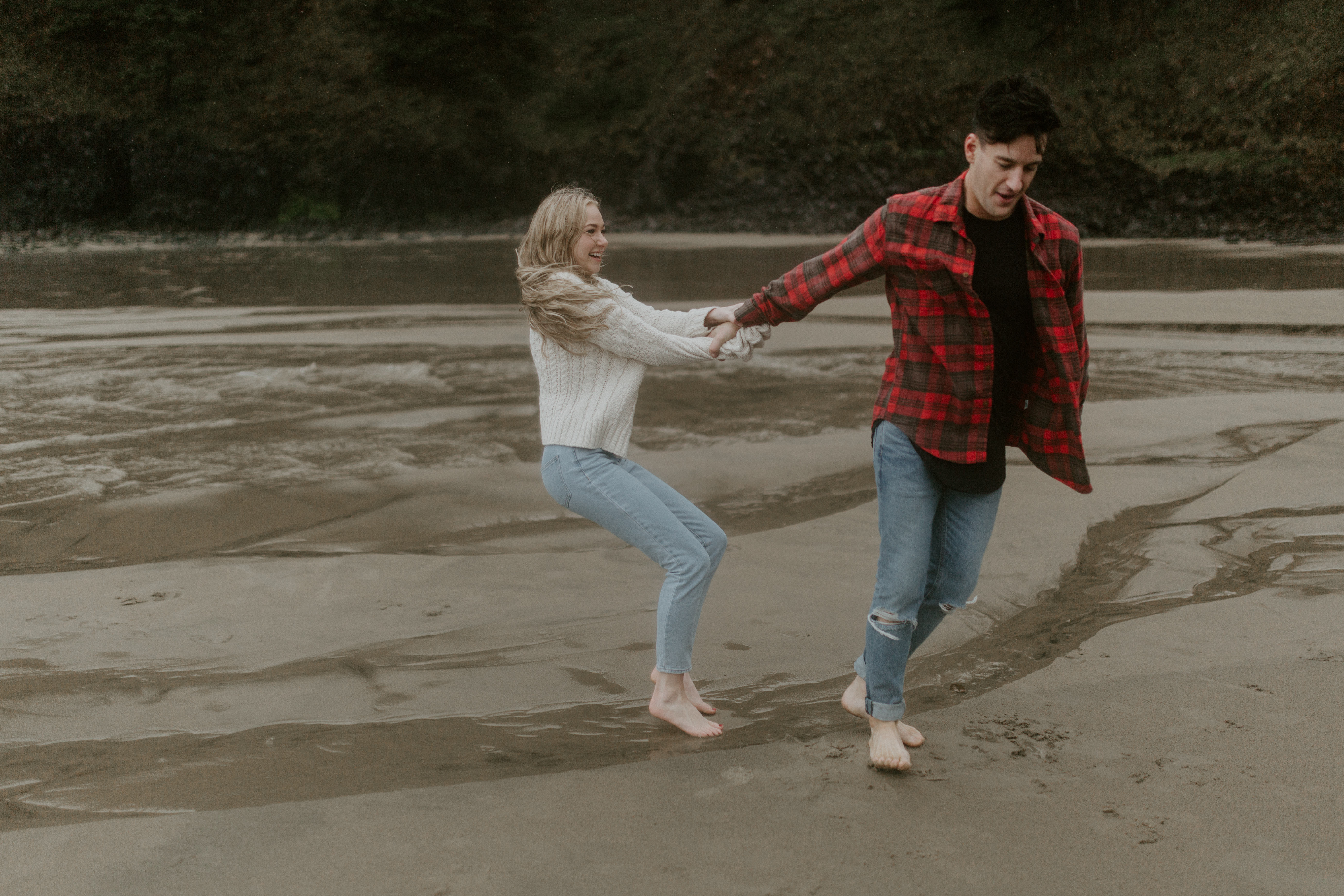 Hannah tries to lift up Grant on Indian Beach in Ecola State Park, Oregon. Engagement photography in Oregon by Sienna Plus Josh.