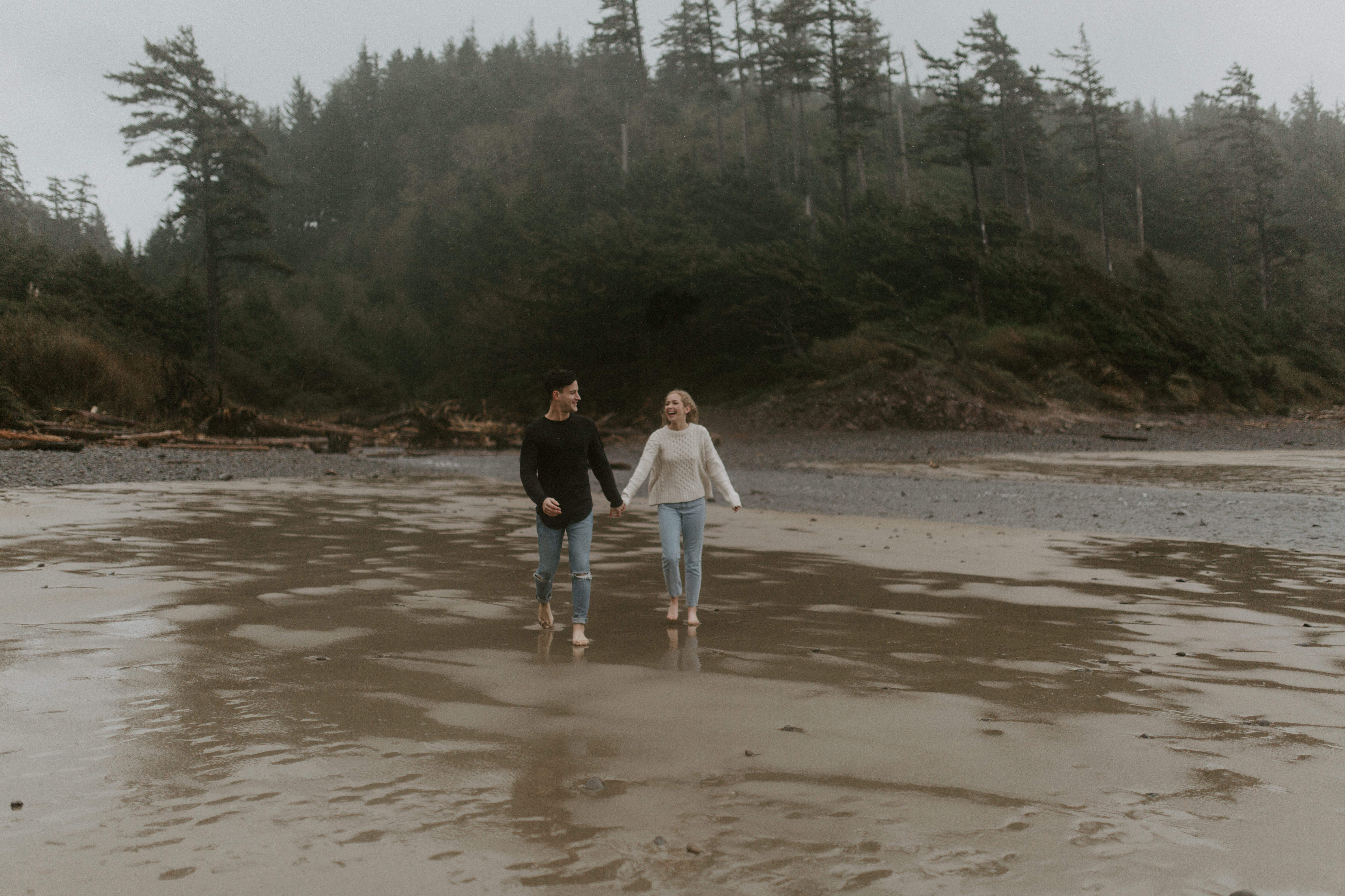 Hannah and Grant hold hands and walk along Indian Beach in Ecola State Park, Oregon. Engagement photography in Oregon by Sienna Plus Josh.