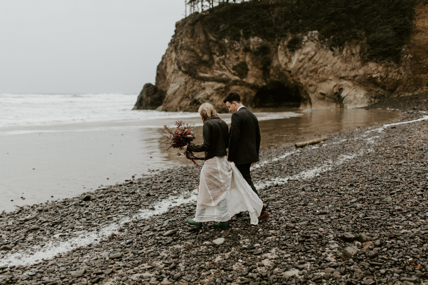 Hannah and Grant walk along the rocky shore of Cannon Beach during their rainy elopement in Oregon. Wedding photography in Portland Oregon by Sienna Plus Josh.