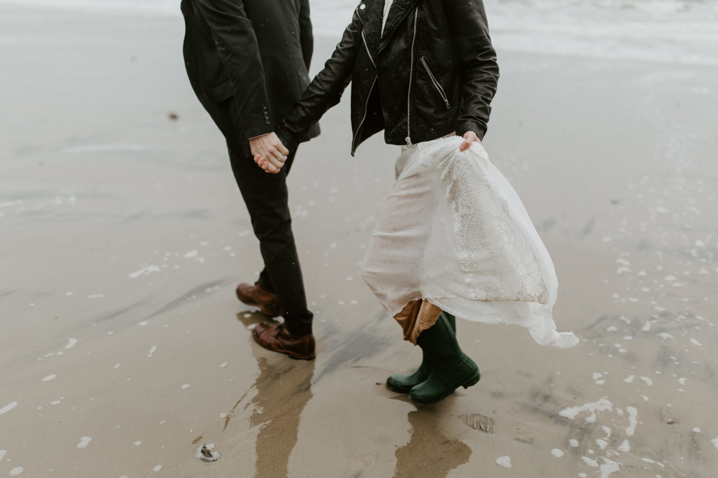 Hannah and Grant walk hand in hand on the sandy shore of Cannon Beach, Oregon. Wedding photography in Portland Oregon by Sienna Plus Josh.