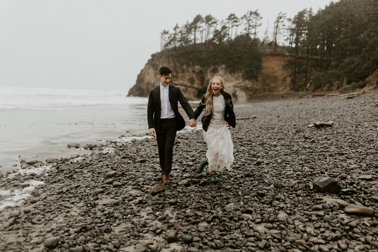 Hannah and Grant walk along the rocks of Hug Point in Cannon Beach, Oregon. Wedding photography in Portland Oregon by Sienna Plus Josh.