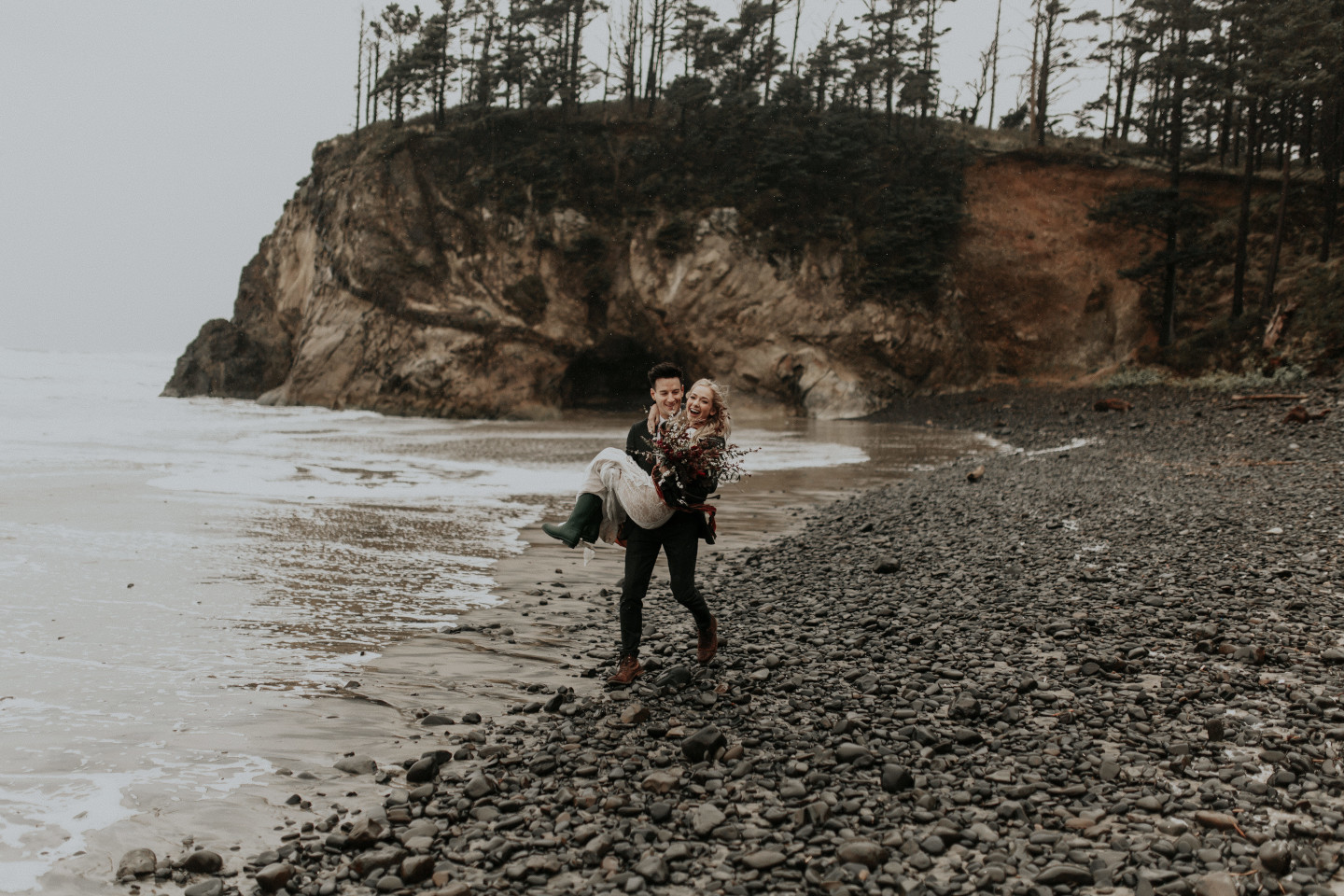 Grant carries Hannah along Cannon Beach in Oregon. Wedding photography in Portland Oregon by Sienna Plus Josh.