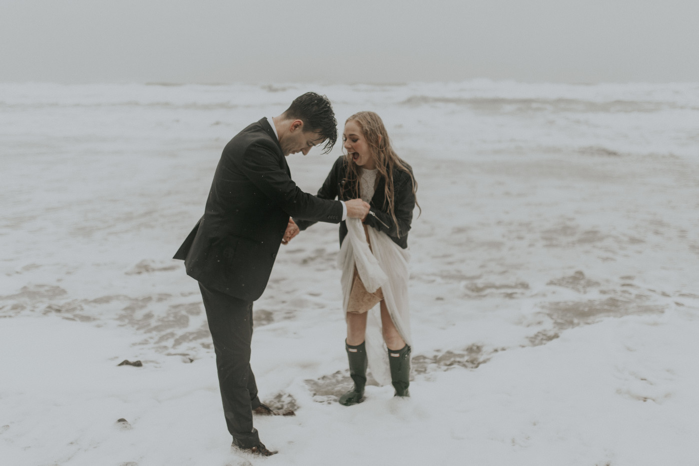 Hannah and Grant get their feet wet at the shore of Hug Point in Cannon Beach, Oregon during their elopement. Wedding photography in Portland Oregon by Sienna Plus Josh.