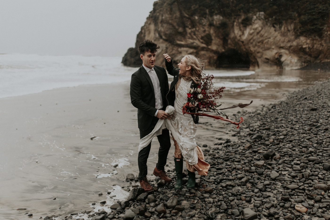 Hannah fixes Grant's fly away hair while they stand on the rocks of Cannon Beach for their Elopement in Oregon. Wedding photography in Portland Oregon by Sienna Plus Josh.