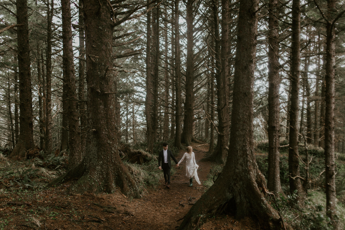 Hannah and Grant walk along the path in the woods at Cannon Beach, Oregon. Wedding photography in Portland Oregon by Sienna Plus Josh.