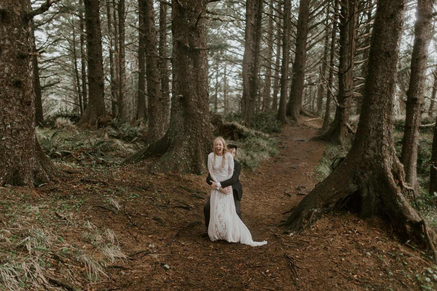 Grant prepares to lift Hannah in the woods of Cannon Beach, Oregon during their Oregon coast elopement. Wedding photography in Portland Oregon by Sienna Plus Josh.