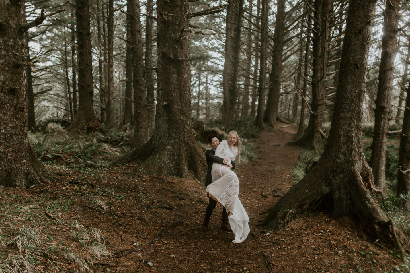 Grant lifts and spins Hannah along a path in Cannon Beach, Oregon. Wedding photography in Portland Oregon by Sienna Plus Josh.