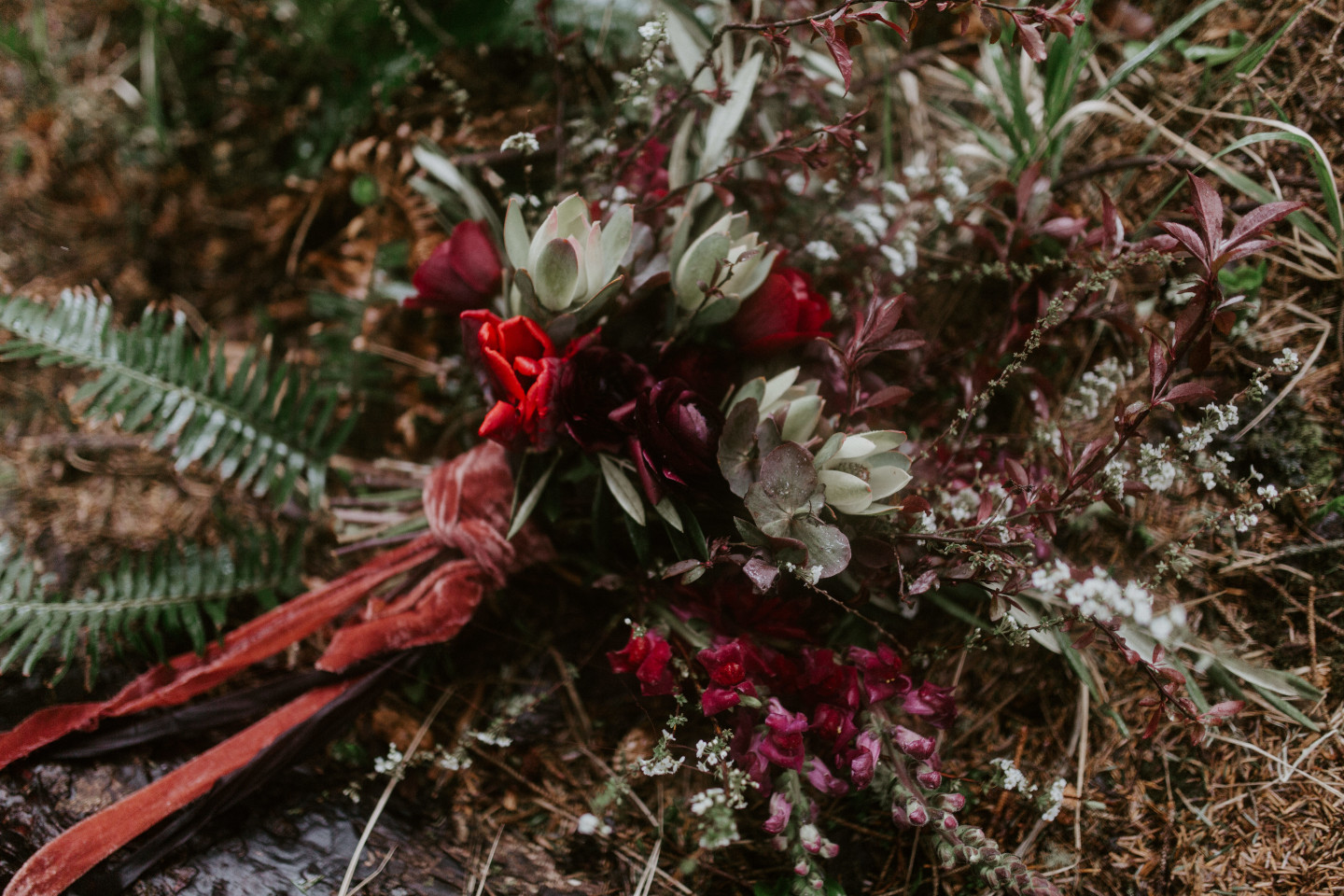 Hannah's bouquet lays on the ground of Cannon Beach, Oregon. Wedding photography in Portland Oregon by Sienna Plus Josh.