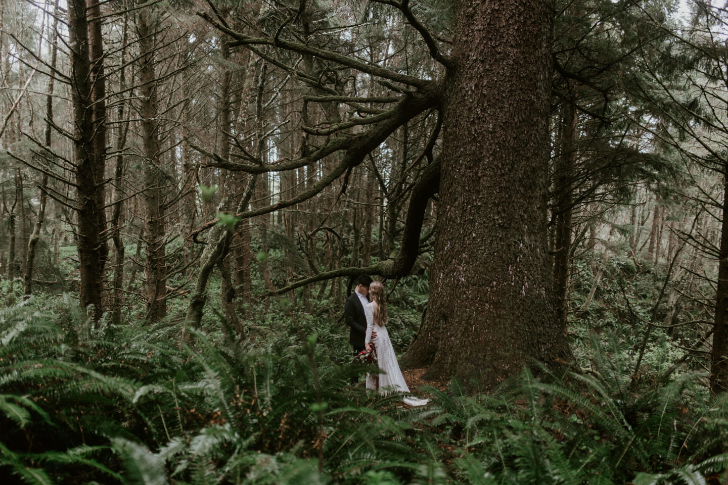 Hannah and Grant stand next to a tree in Cannon Beach, Oregon for their Oregon coast elopement. Wedding photography in Portland Oregon by Sienna Plus Josh.