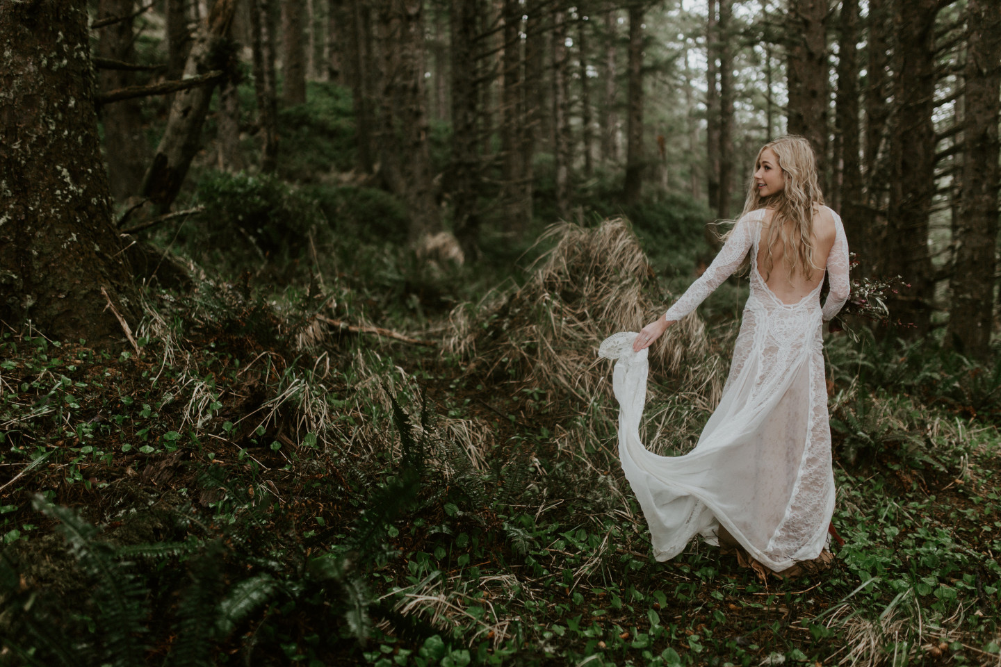Hannah moves her dress as she walks through the woods in Cannon Beach, Oregon during her Oregon coast elopement. Wedding photography in Portland Oregon by Sienna Plus Josh.