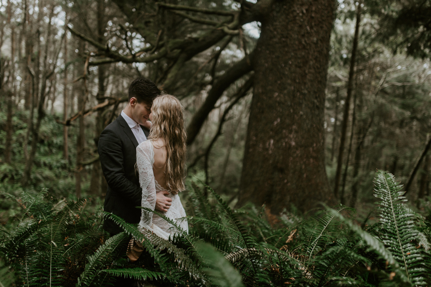 Hannah and Grant stand in the ferns in Cannon Beach, Oregon for their Oregon coast elopement. Wedding photography in Portland Oregon by Sienna Plus Josh.