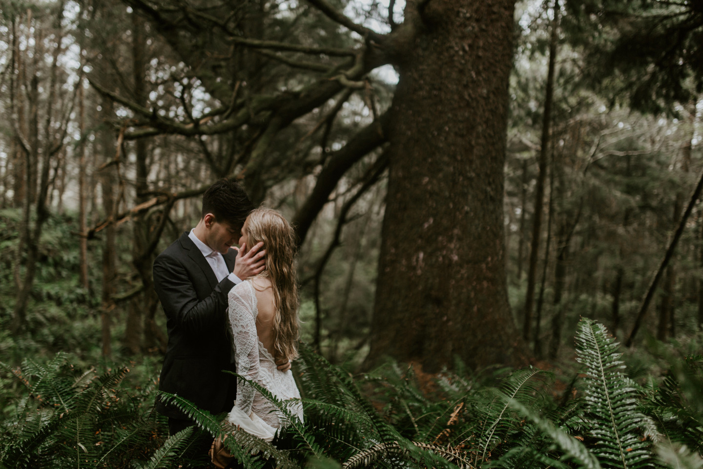Hannah and Grant stand in the ferns in Cannon Beach, Oregon. Wedding photography in Portland Oregon by Sienna Plus Josh.