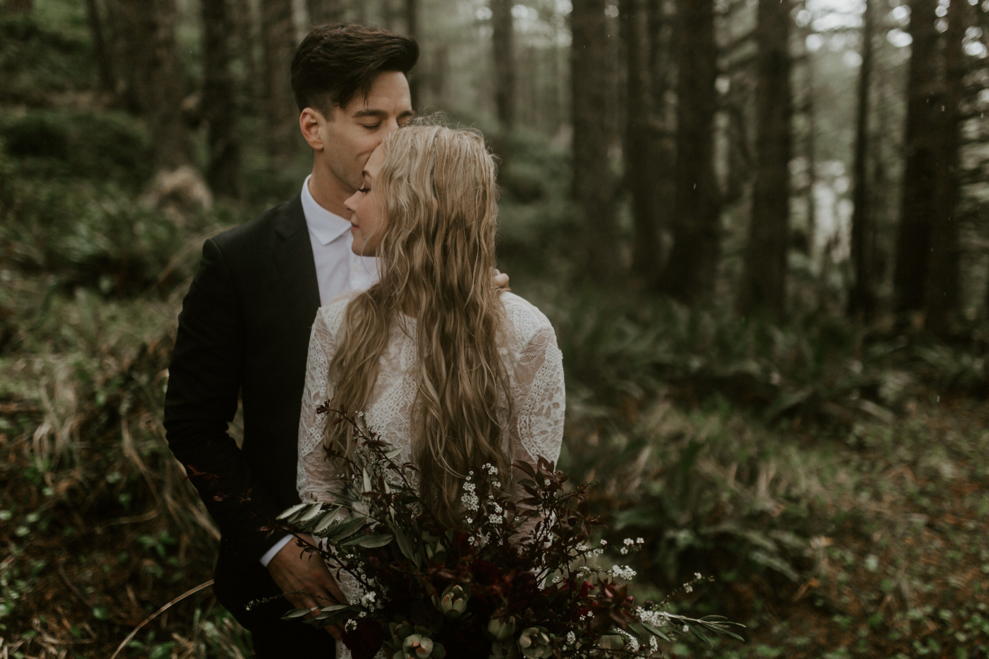 Hannah Grant hug in the treeline of Cannon Beach, Oregon during their elopement. Wedding photography in Portland Oregon by Sienna Plus Josh.