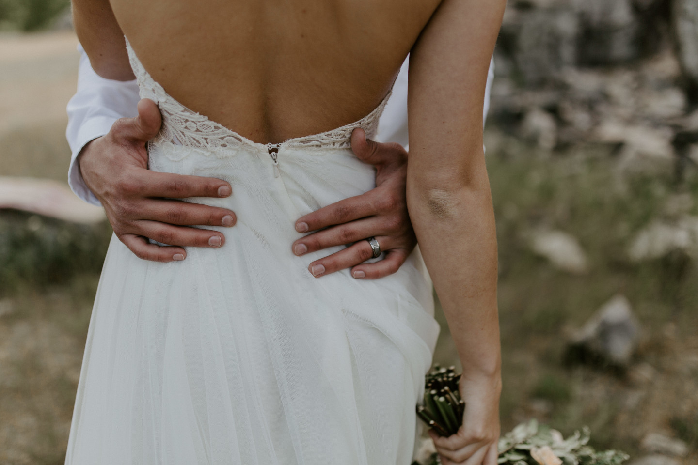 A close up of Harper's back while Trevor puts his arms around her at Cascade Locks, Oregon. Elopement photography in Portland Oregon by Sienna Plus Josh.