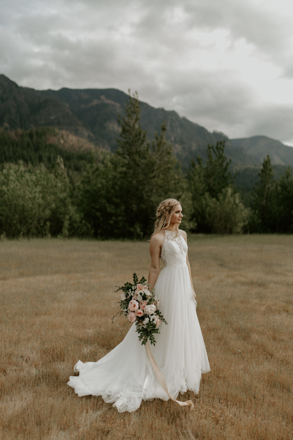 Harper stands alone with her boquet at the Columbia River Gorge in Oregon. Elopement photography in Portland Oregon by Sienna Plus Josh.