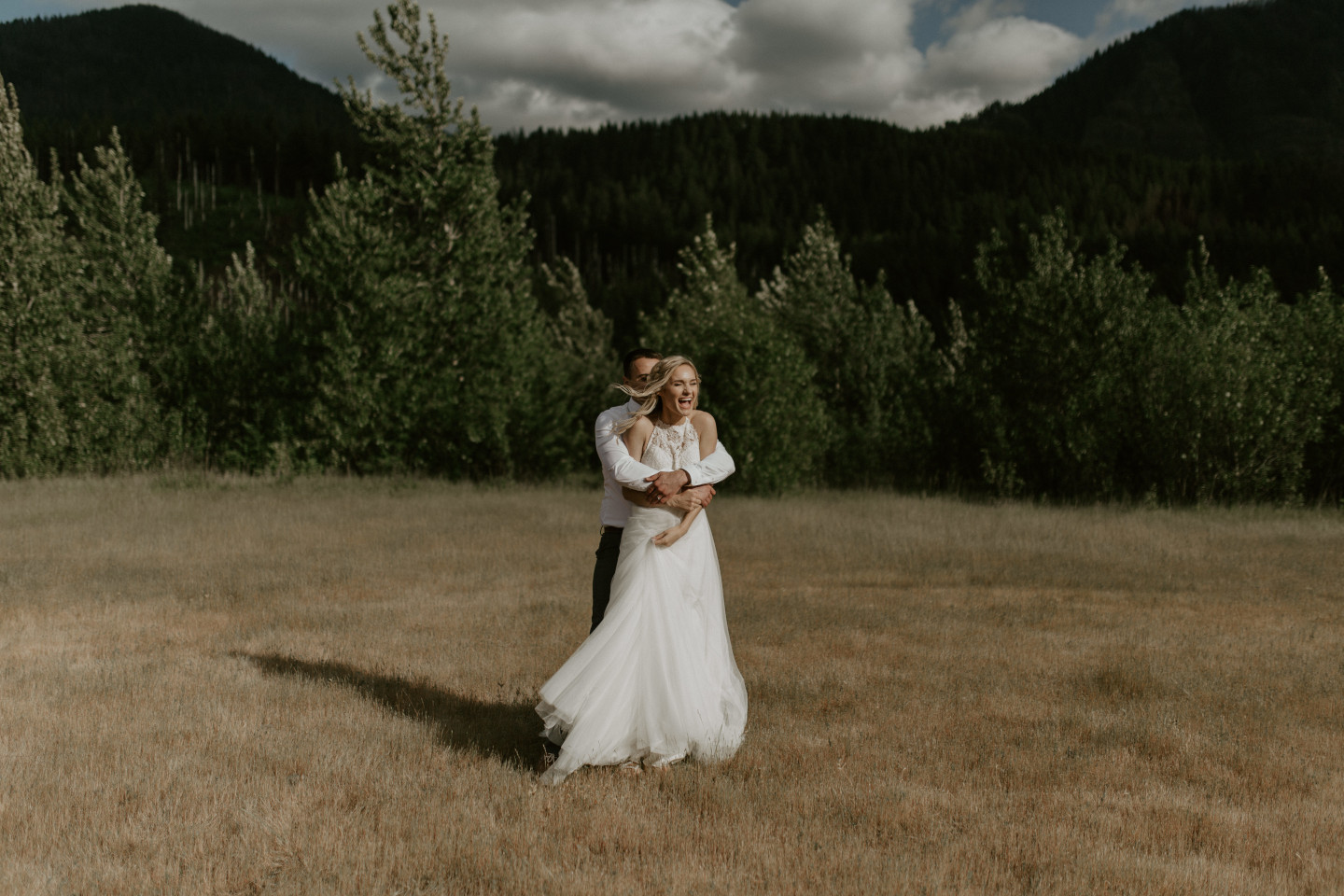 Trevor holds Harper from behind at the Columbia Gorge, Oregon. Elopement photography in Portland Oregon by Sienna Plus Josh.