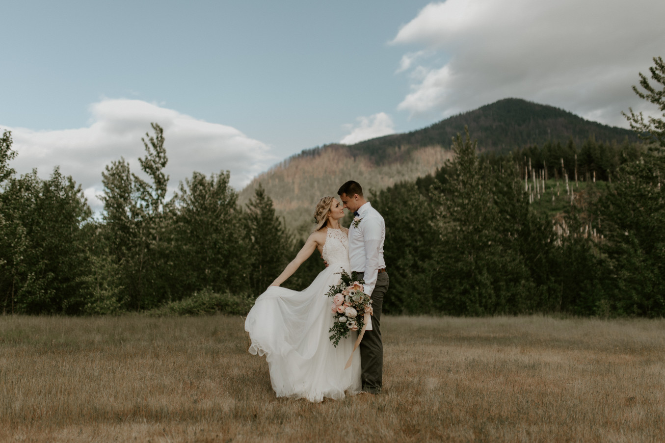 Harper holds her dress while facing Trevor at the Columbia Gorge, Oregon. Elopement photography in Portland Oregon by Sienna Plus Josh.