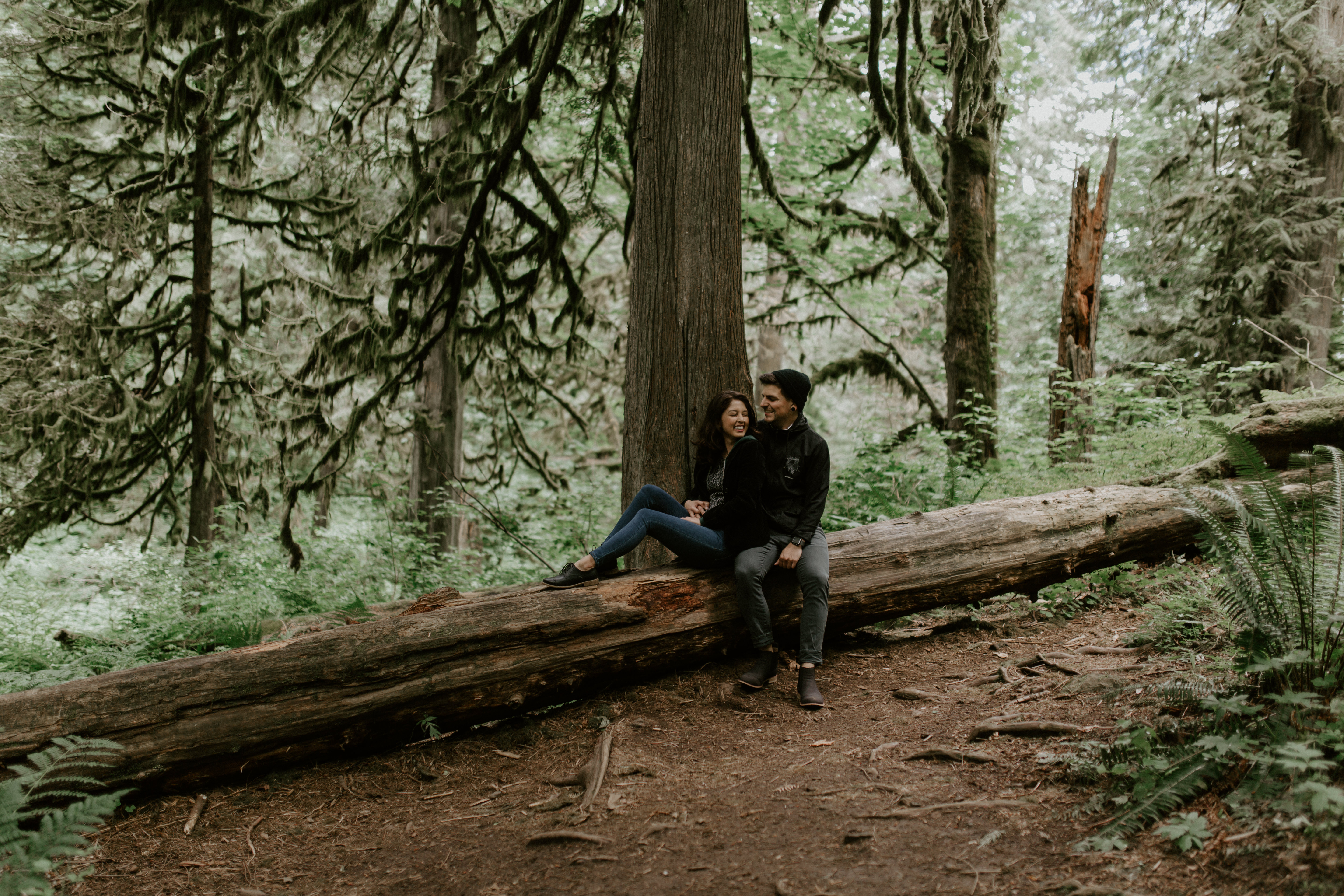 Jasmine and Chris sit on a downed tree at Latourell Falls, Oregon. Adventure photography in Portland Oregon by Sienna Plus Josh.