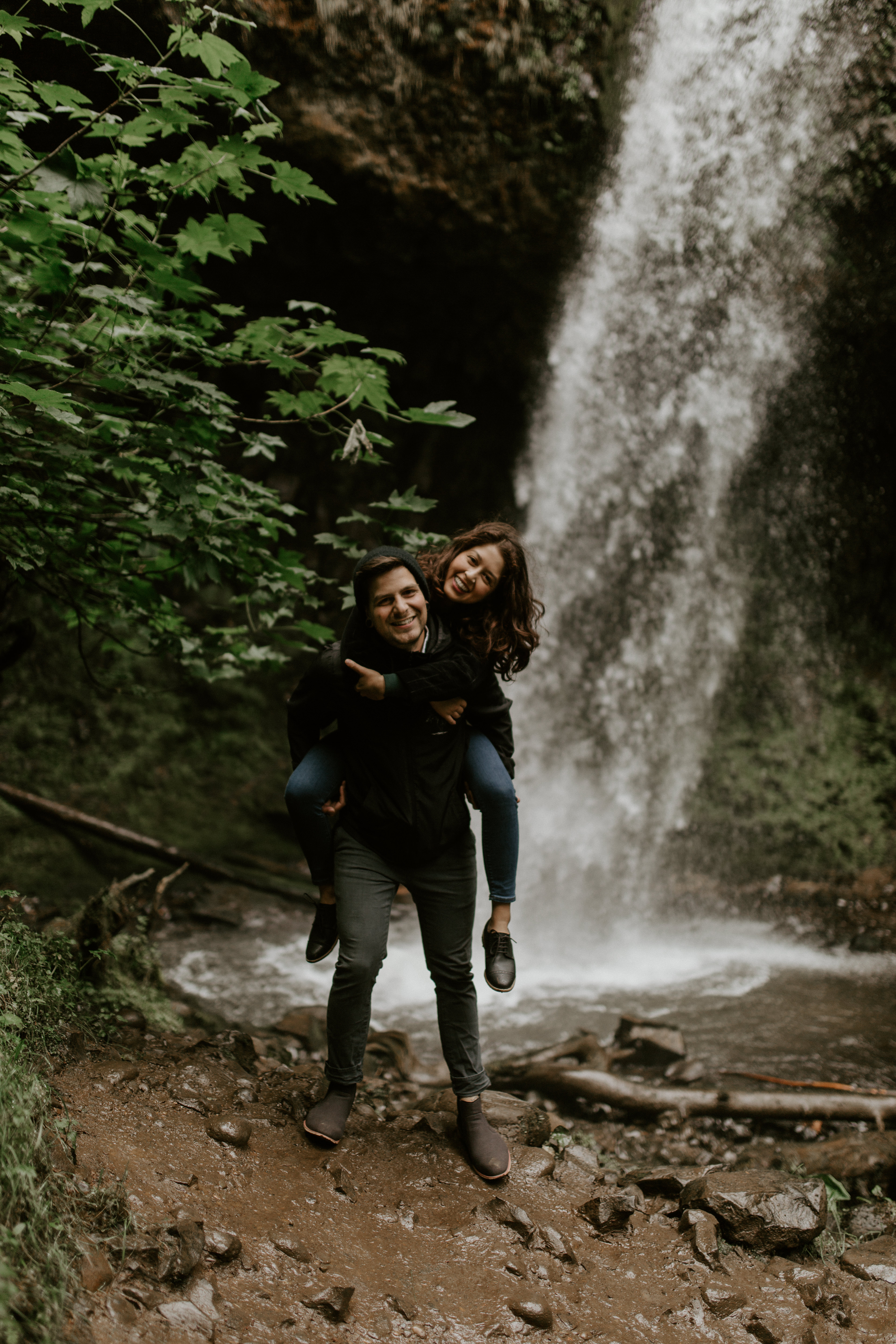 Chris gives Jasmine a piggy back ride in front of the upper falls of Latourell at the Columbia River Gorge in Oregon for her Oregon Adventure. Adventure photography in Portland Oregon by Sienna Plus Josh.