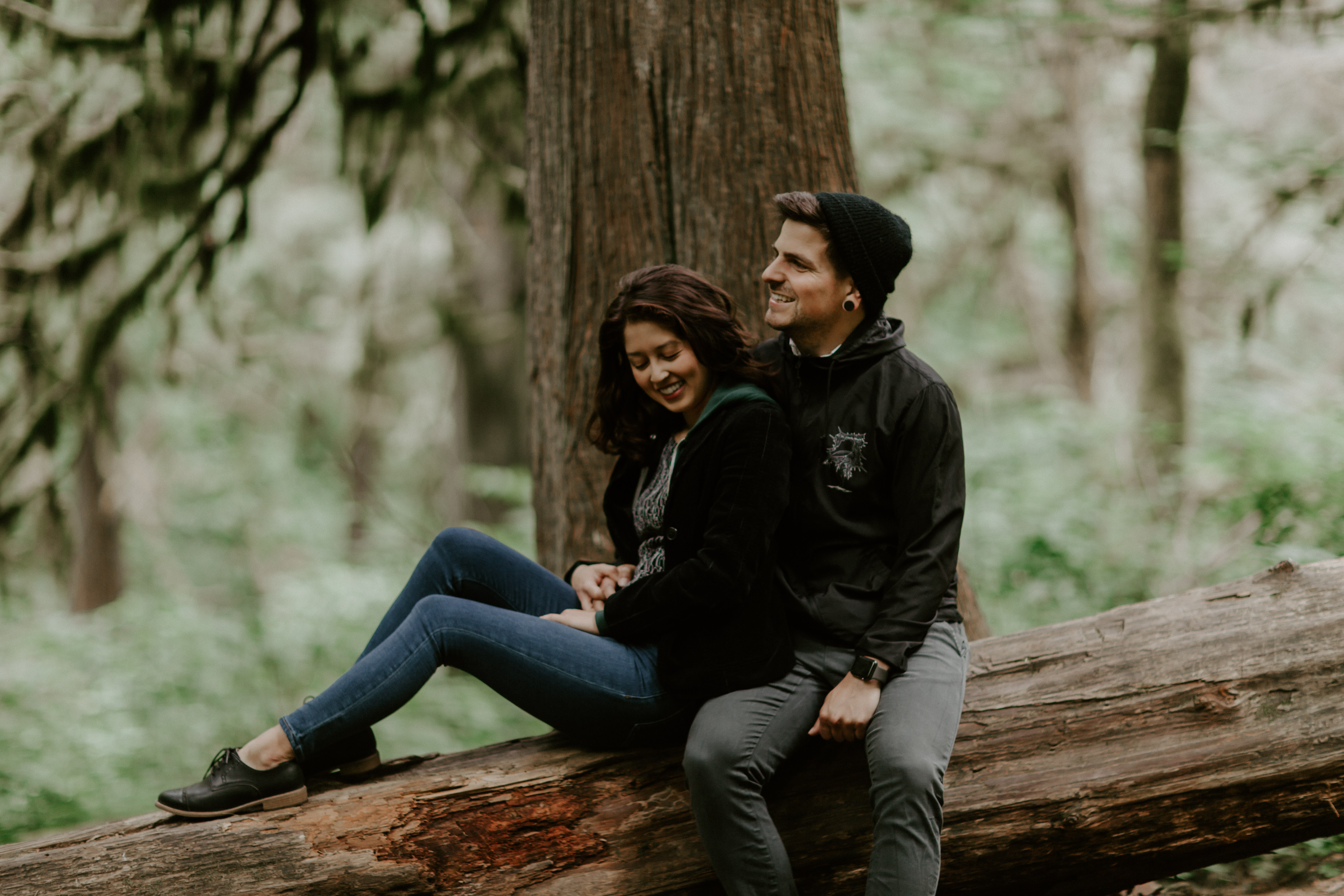 Jasmine and Chris sit on a downed tree along the trail at Latourell Falls in Oregon. Adventure photography in Portland Oregon by Sienna Plus Josh.