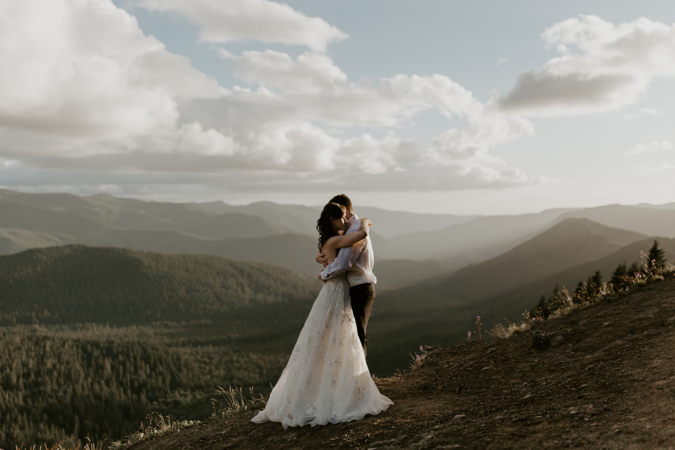 Moira and Ryan stand near a cliff with the view of the mountains in the background. Adventure elopement wedding shoot by Sienna Plus Josh.