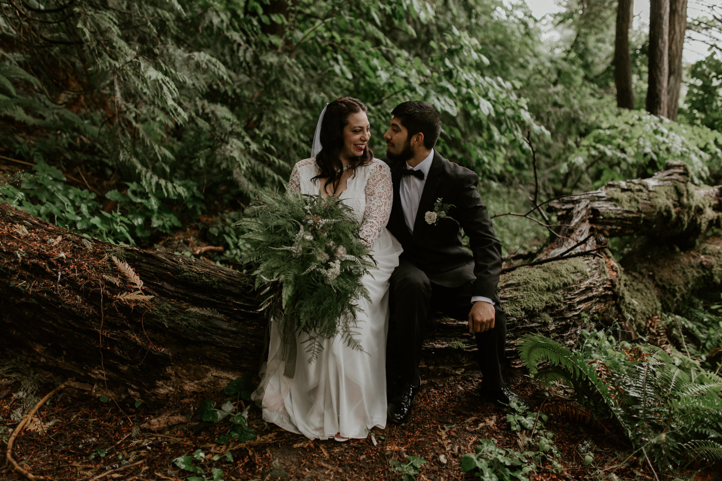Sam and Sarah sit next to each other on a log at the Columbia River Gorge in Oregon for her Oregon Adventure. Elopement photography in Portland Oregon by Sienna Plus Josh.