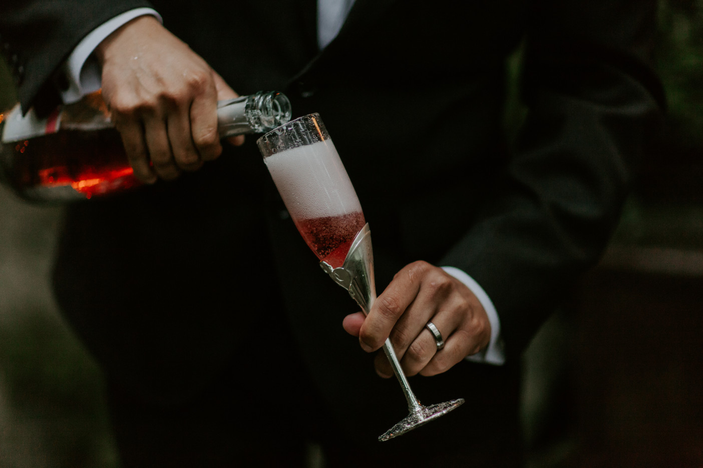 Sam pours a bottle of champagne at Skamania House, Washington. Elopement photography in Portland Oregon by Sienna Plus Josh.
